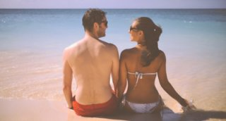 Cute Man And Woman Sitting On A Beach With SeaSmall